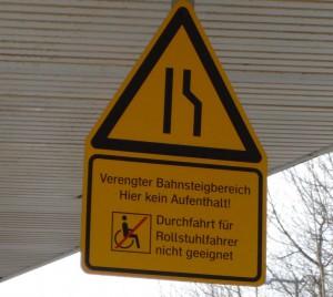 Warnhinweis-Schild für Rollstuhlfahrer am Bahnhof Zorneding